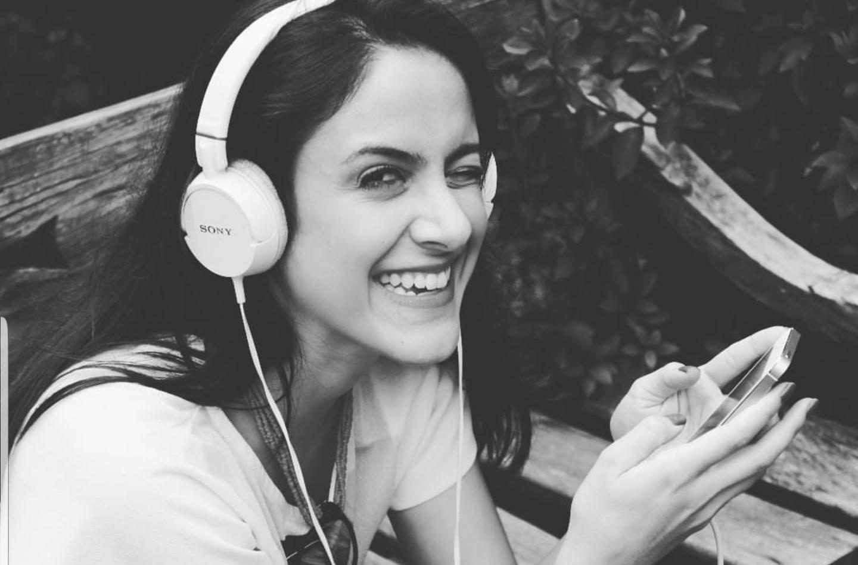 Mulher ouvindo podcast no fone e sorrindo