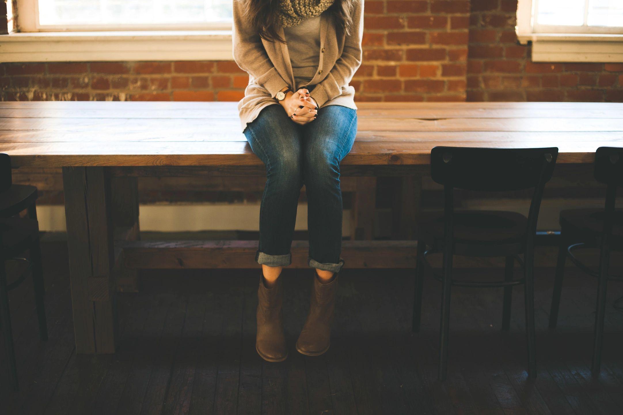 mulher sozinha em cima de mesa