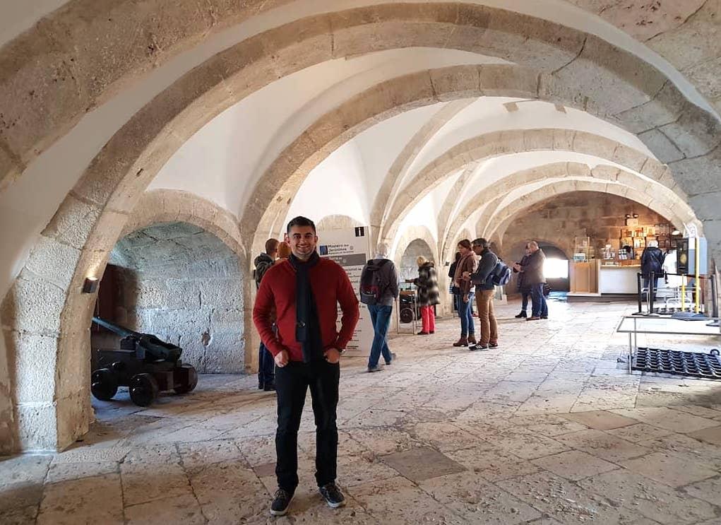 Homem dentro da Torre de Belém com canhões ao fundo