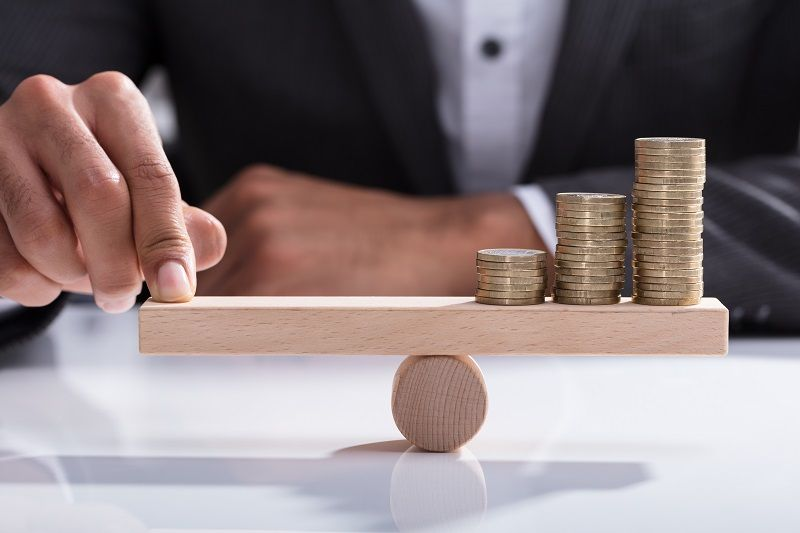 Businessperson-Balancing-Stacked-Coins-On-Wooden-Seesaw-cm