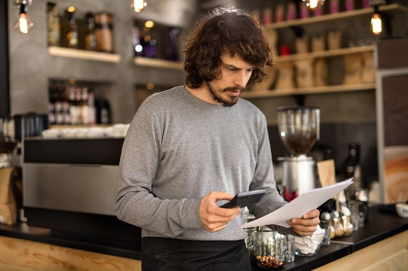 Serious-barista-calculating-finances-in-a-cafe-cm