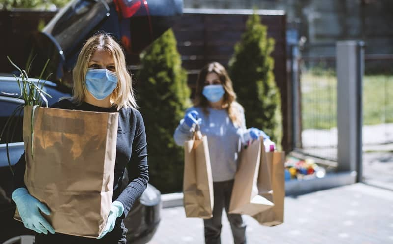 Women buying groceries and back home. Wearing protective mask and gloves-cm