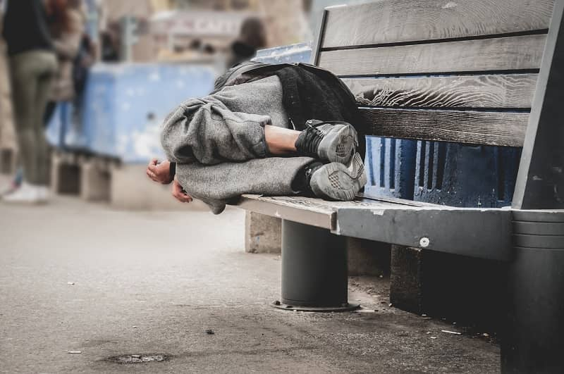 Poor homeless man or refugee sleeping on the wooden bench on the urban street in the city, social documentary concept, selective focus-cm