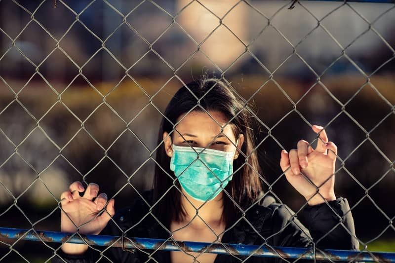 Conceptual photo of captivity with young adult woman on it. Coronavirus concept. Girl wearing protective mask.-cm