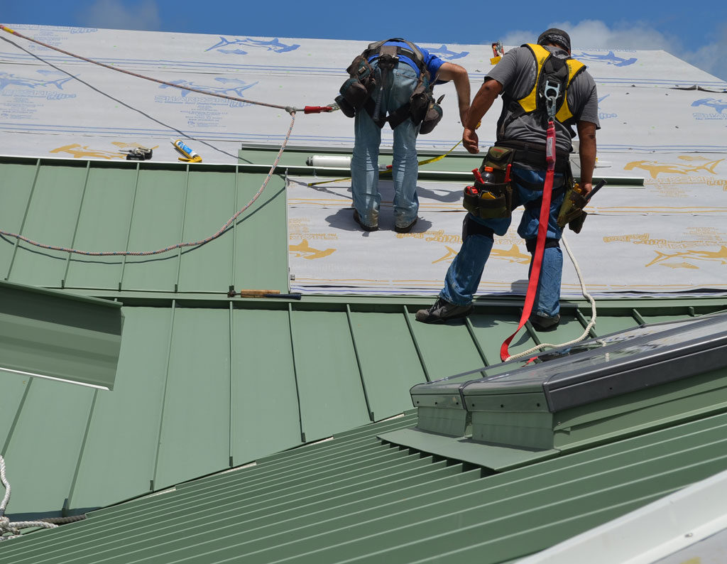 Green standing seam aluminum roof being installed over the Sharkskin Ultra Radiant®