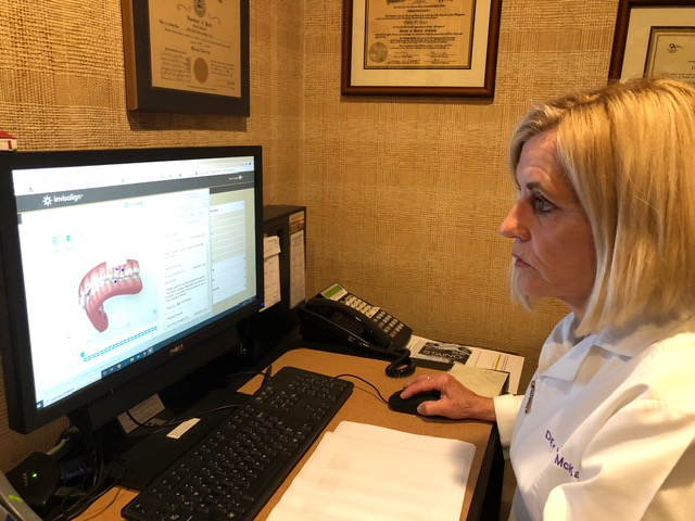 Dr. McKay studies the Invisalign scan to formulate the treatment plan that will give her patient's the smile they always wanted