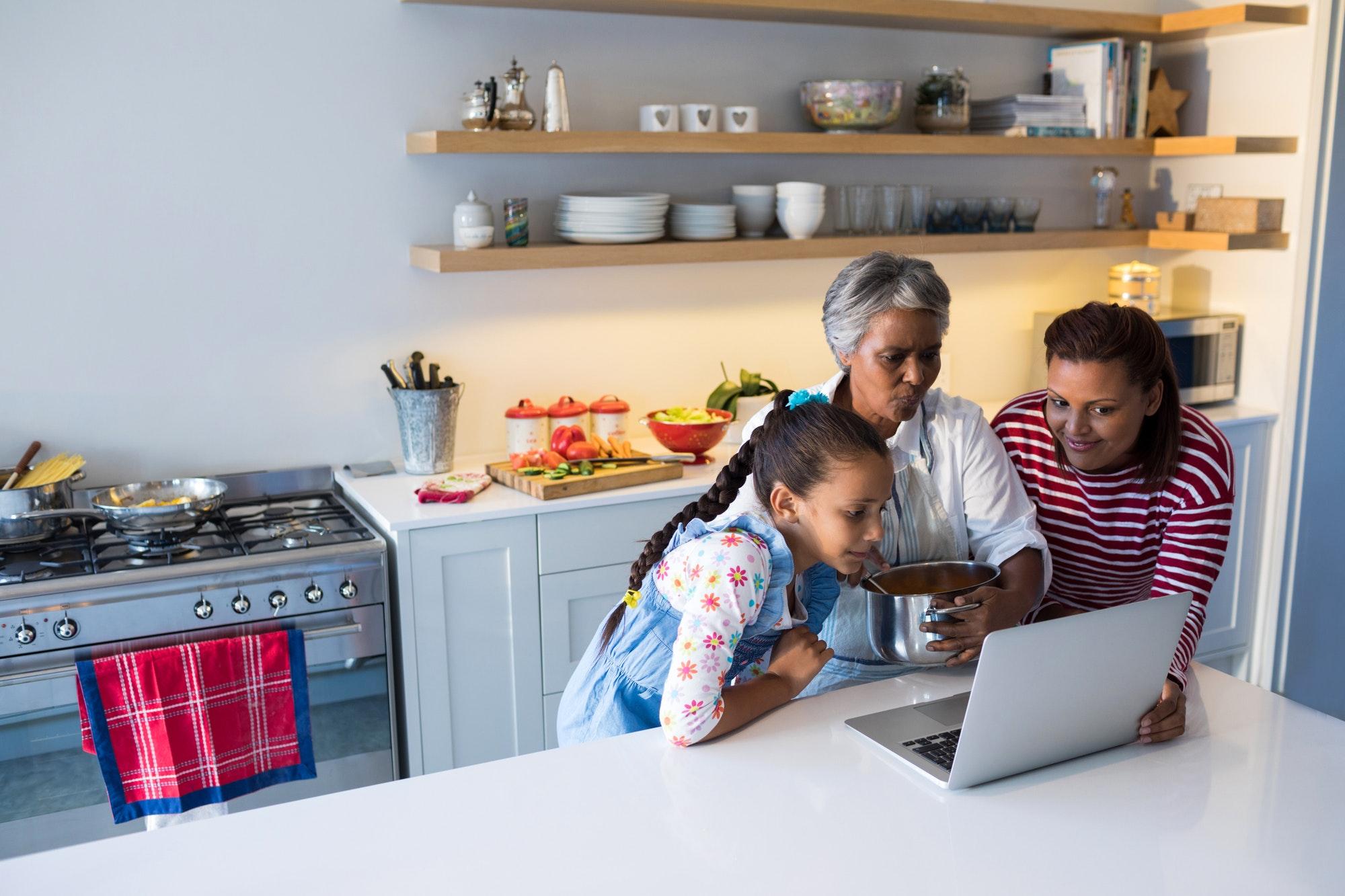 Happy family using laptop in kitchen worktop
