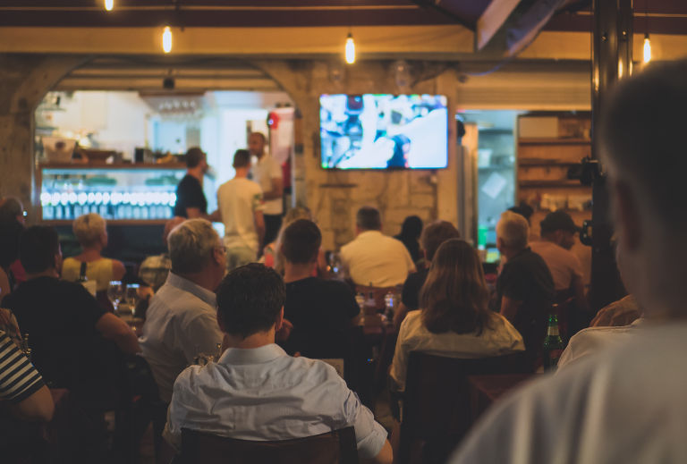 patrons watching sports on tv in bar