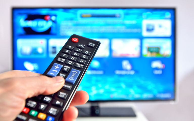 Smart remote in man's hand pointing at tv