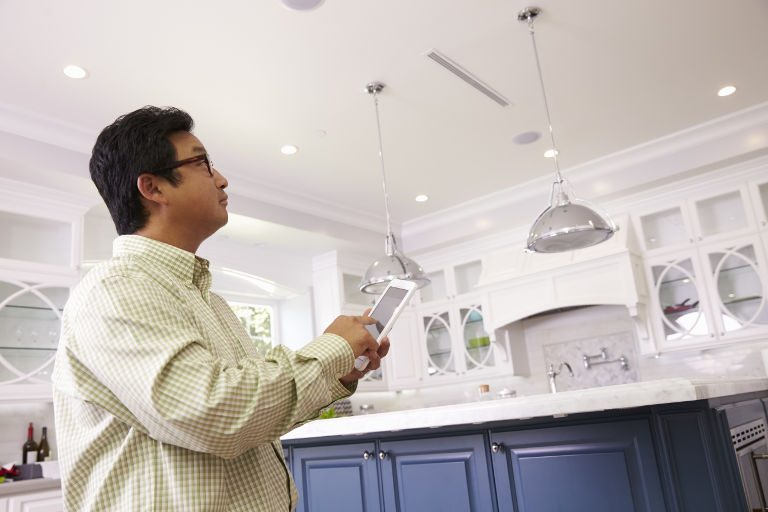 Man Using Digital Tablet To Control Lighting At Home