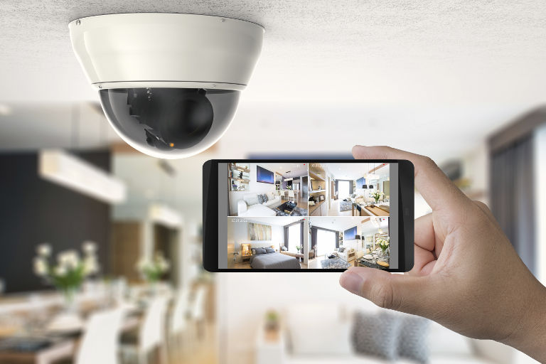 hand holding phone monitor with security camera