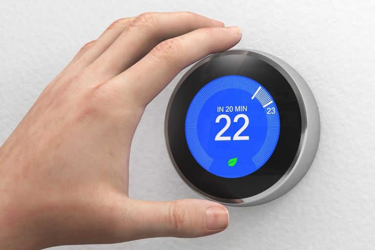 man's hand adjusting the thermostat