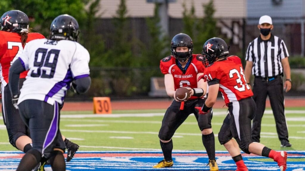 Heather Marini of the Boston Renegades hands a football to teammate Alison Gauvin