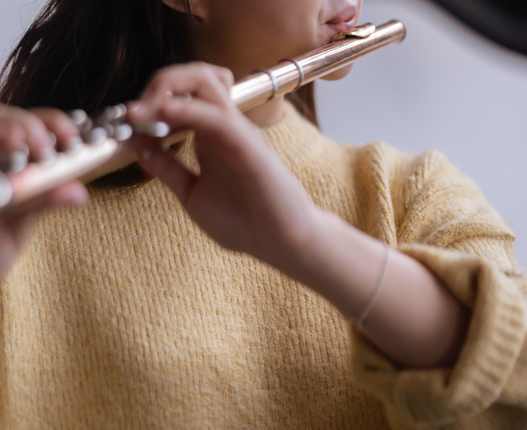 A woman in a yellow sweater with rolled-up sleeves practices the flute