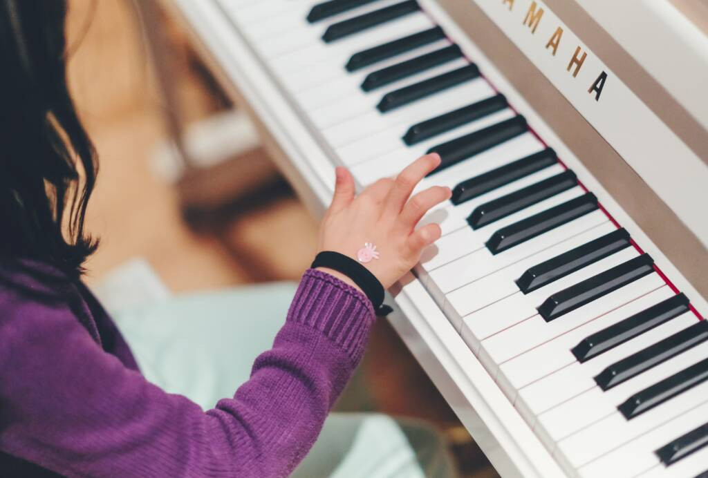 A woman in a purple sweater plays the piano with her right hand.