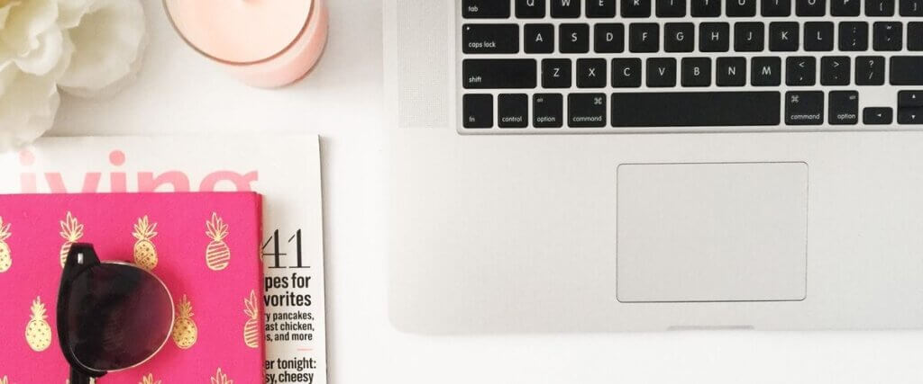 flat lay image of mac book and pink notebook on desk