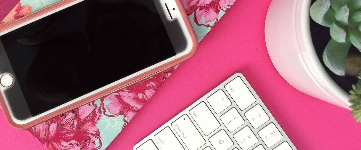 pink desk flatlay with iphone, notebook, and keyboard