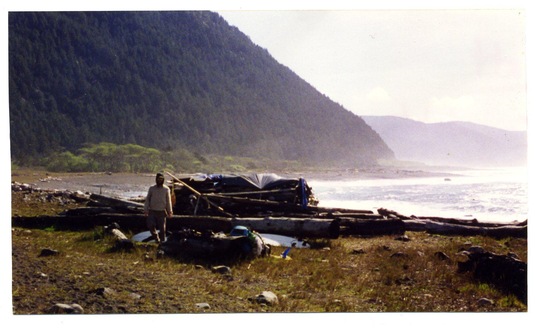 Artist Matt Beard emerging from a makeshift log shelter on the Lost Coast of Northern California circa 1996