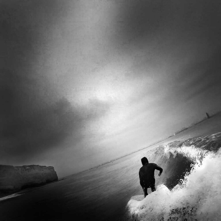 Artist Matt Beard crouches down the line on a small wave in Southern California