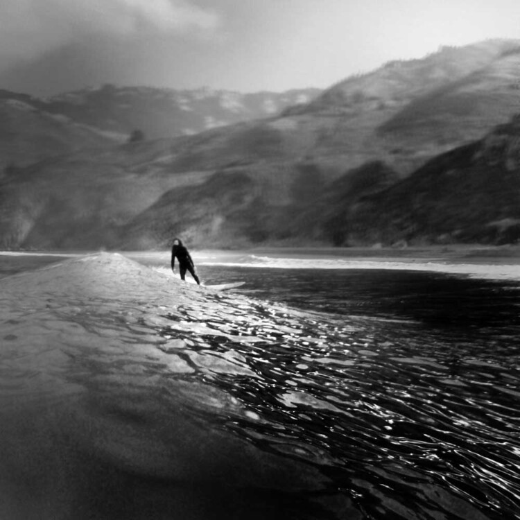 Artist Matt Beard leans into small wave while surfing off the Big Sur Coast of California