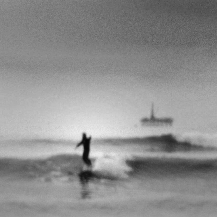 A blurry shot of artist Matt Beard surfing off the coast of Southern California with oil rig platform in the distance