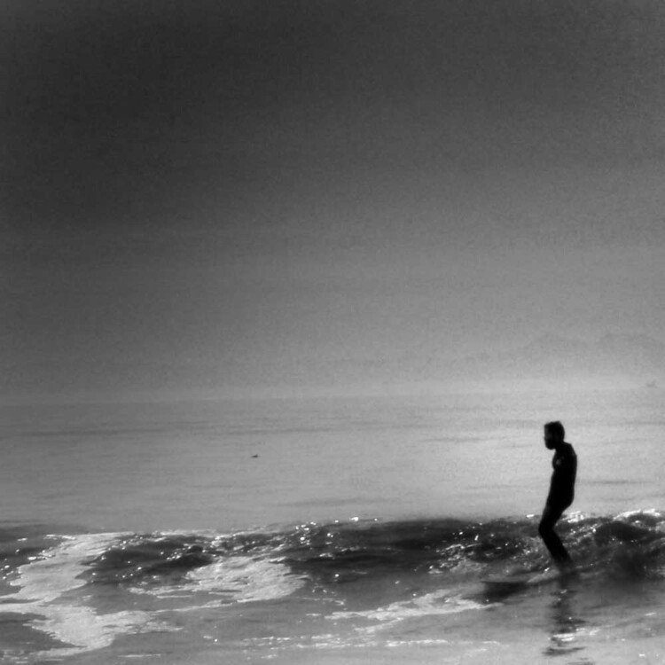 California artist Matt Beard standing absolutely still while surfing a glassy wave in southern California