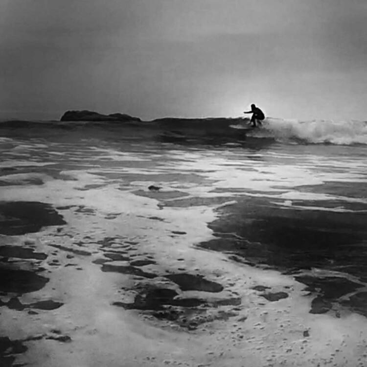 Artist Matt Beard zipping down the line while surfing in Northern California