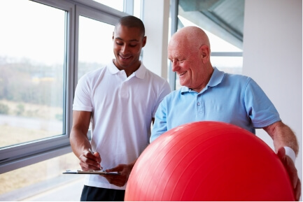 therapist with patient holding swiss ball