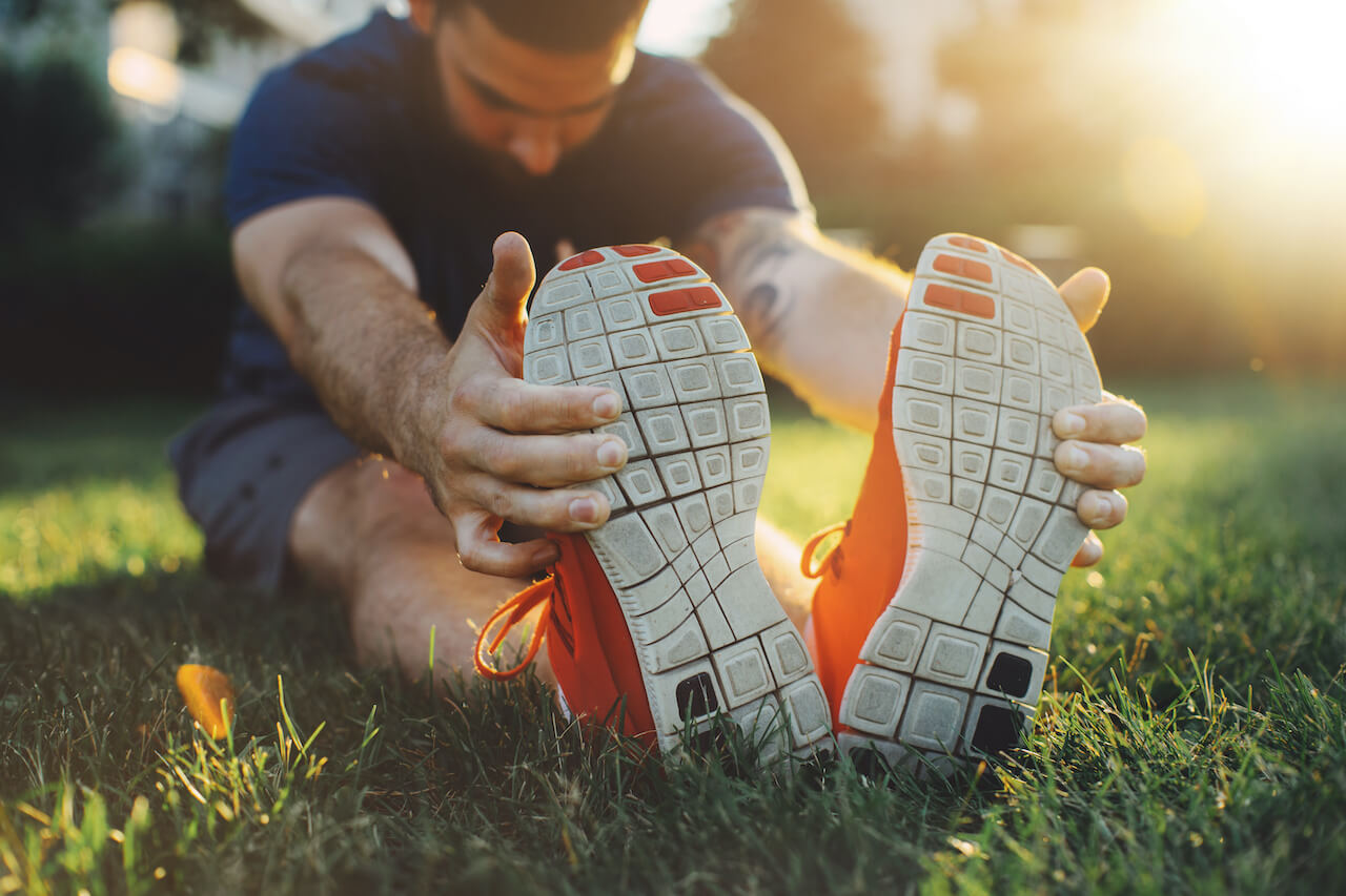 Man stretching in the park before running at the sunset focus on shoes