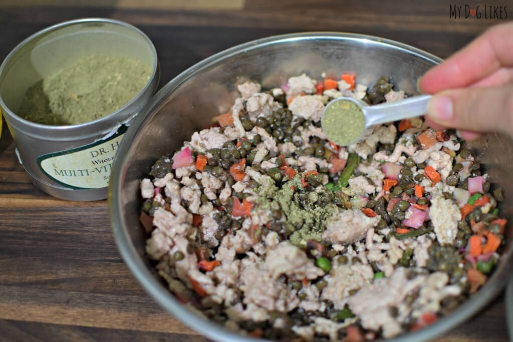 Adding a multi-vitamin to our homemade dog food.