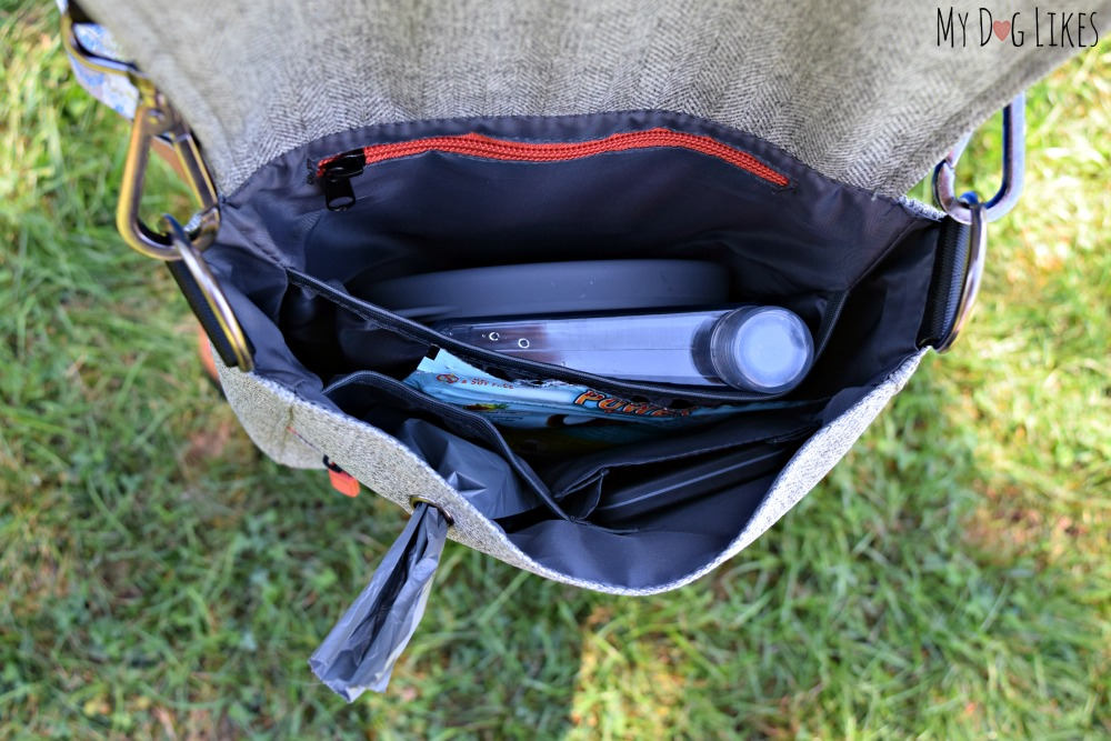 Plenty of space inside and includes a flat water bottle, collapsible bowl, and poop bag dispenser.