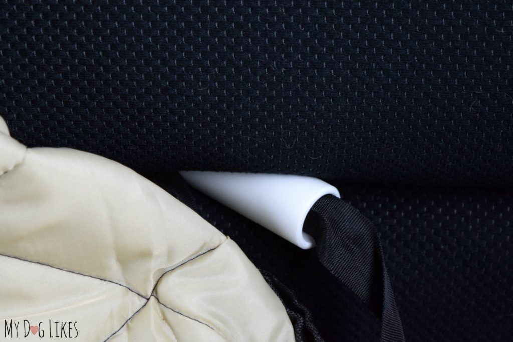 Inserting the anchors into the seat crack to keep the cover secure.