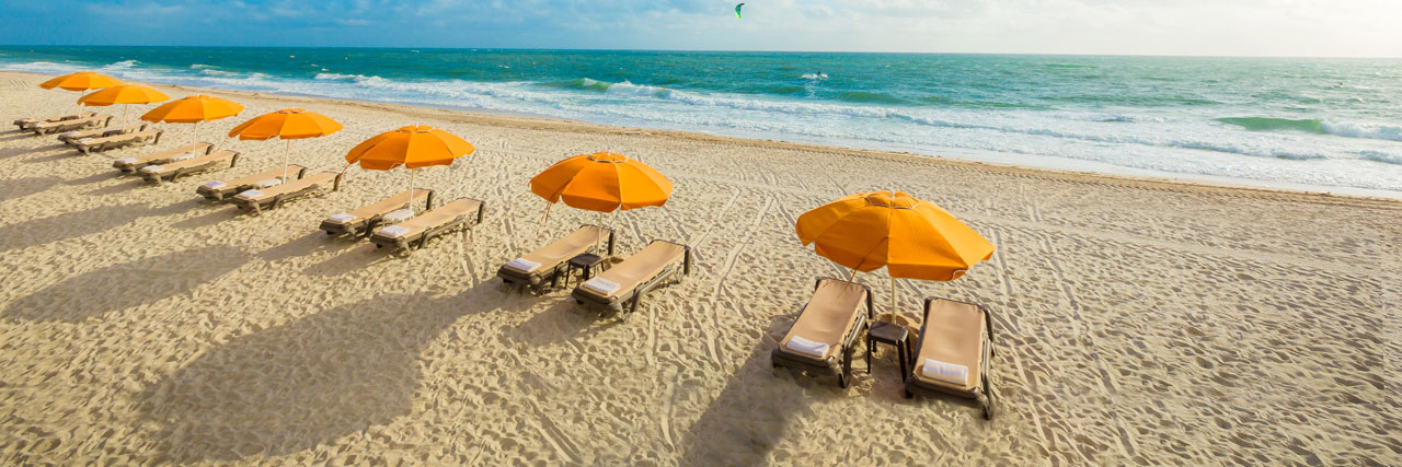 Orange Umbrellas with two lounge chairs each on the beach with view of Atlantic Ocean