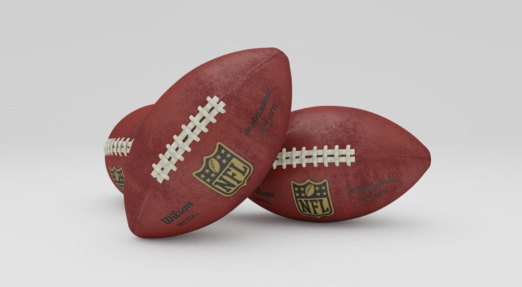 Super Bowl Trophy and two NFL footballs
