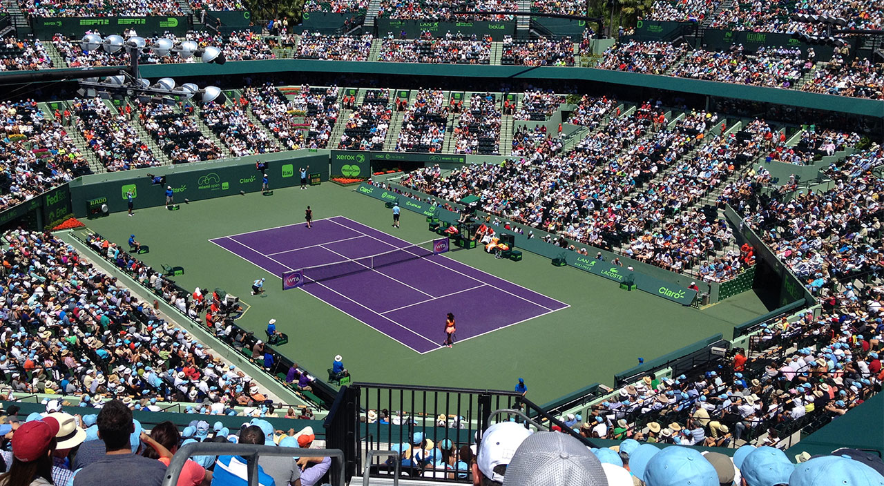 Visit Fort Lauderdale this spring for the Miami Open. Image shows purple tennis court with large audience in attendance