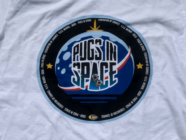 Close up image of a the pugs in space federation of canines logo on a plain white t-shrit