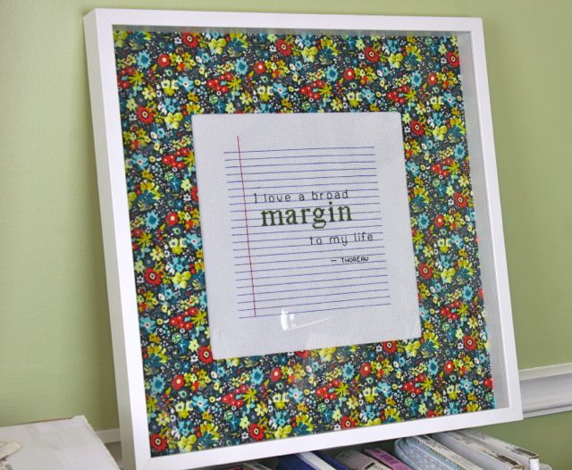 framed cross stitch with fabric covered mat