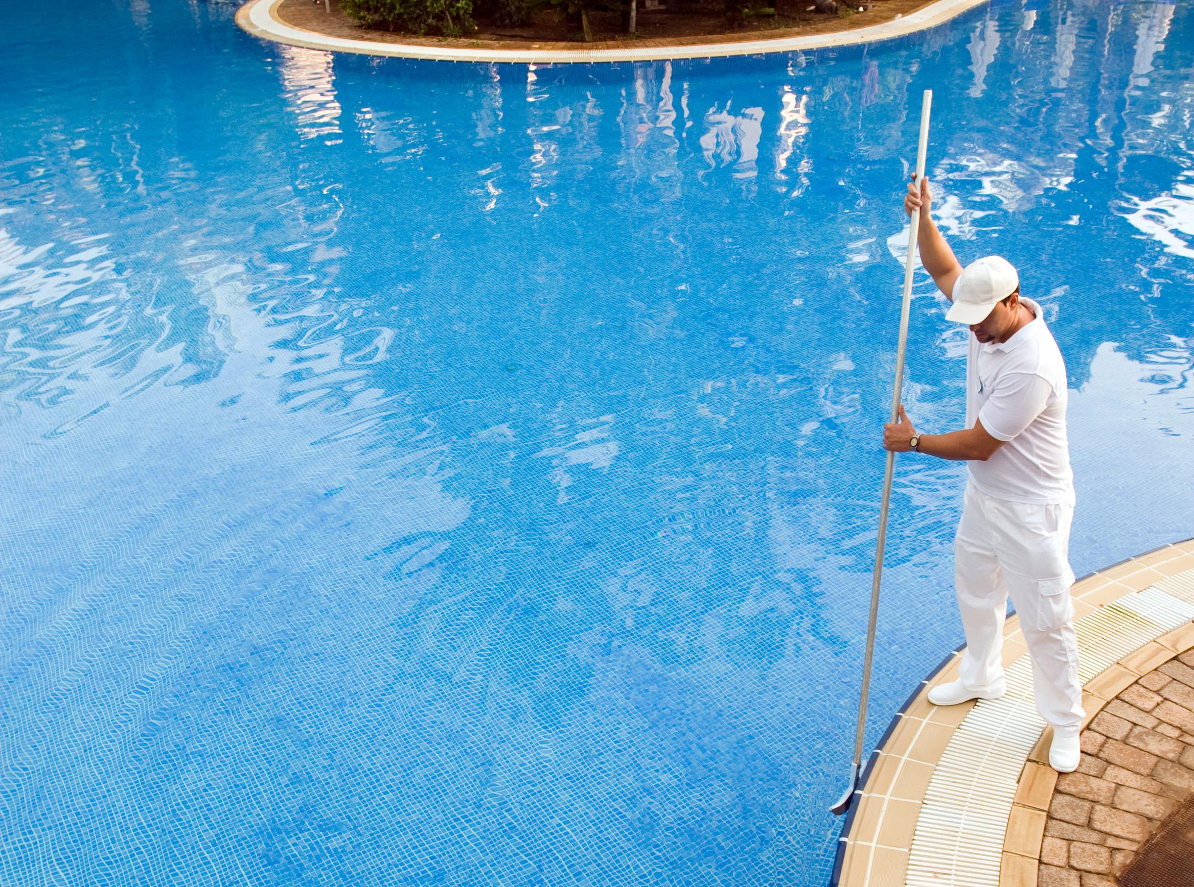 swimming pool guy sweeping the pool's walls
