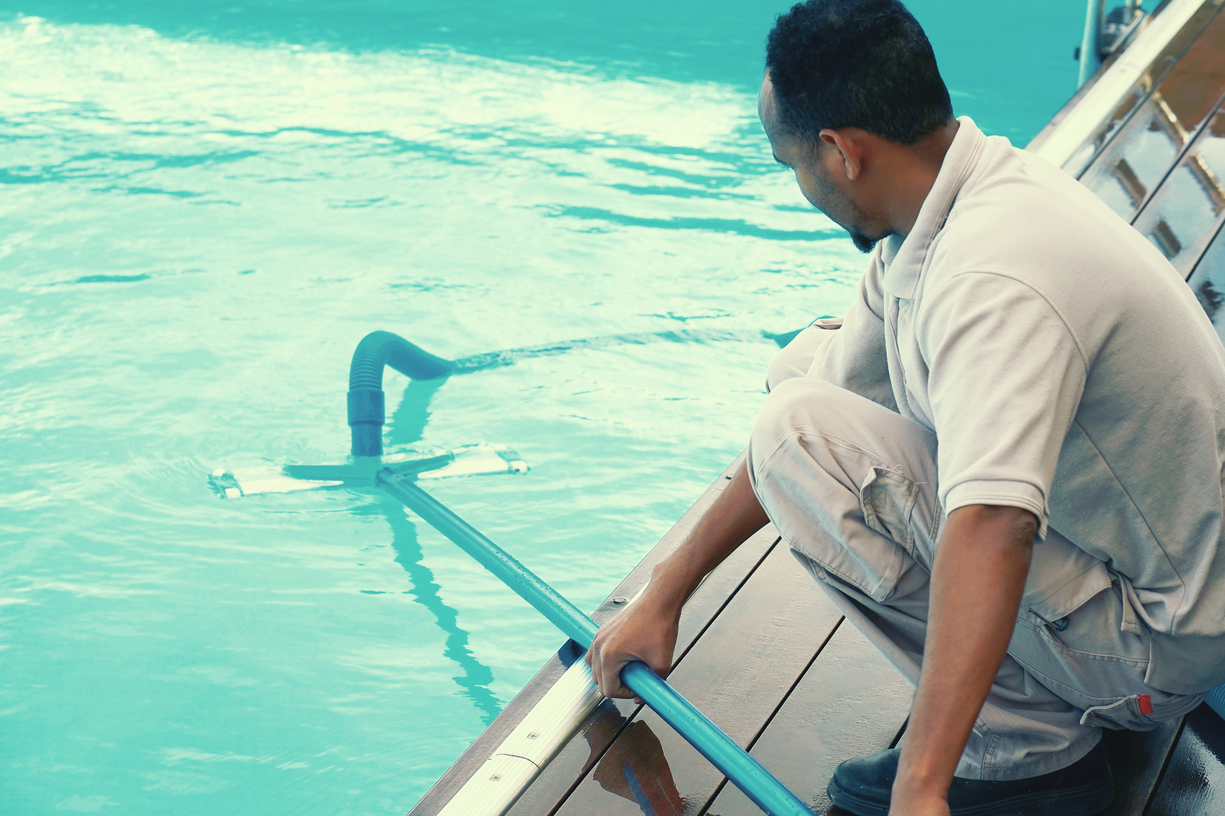 swimming pool technician giving maintenance to a swimming pool