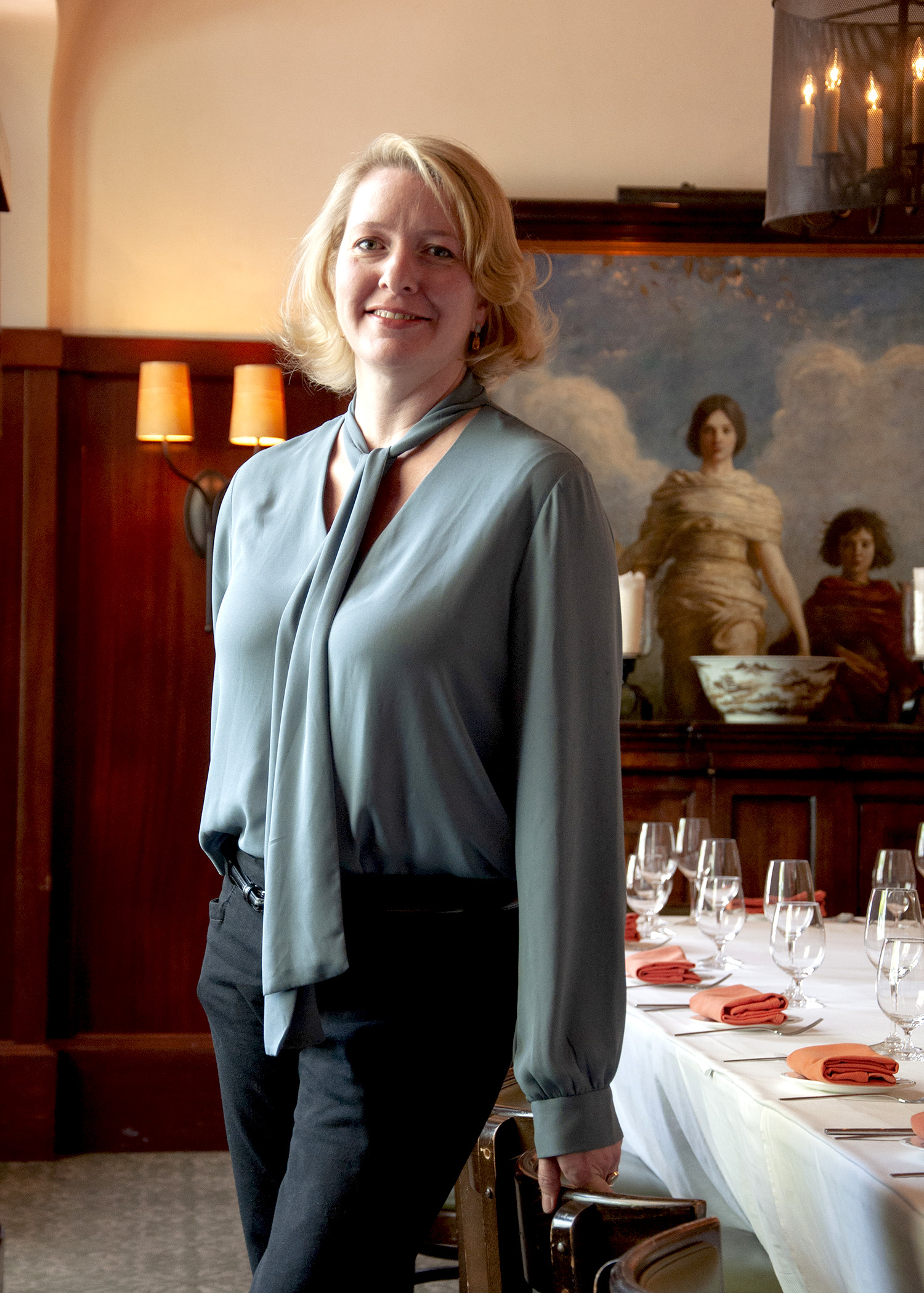 Ingrid French standing in front of table at Cinghiale's private dining room