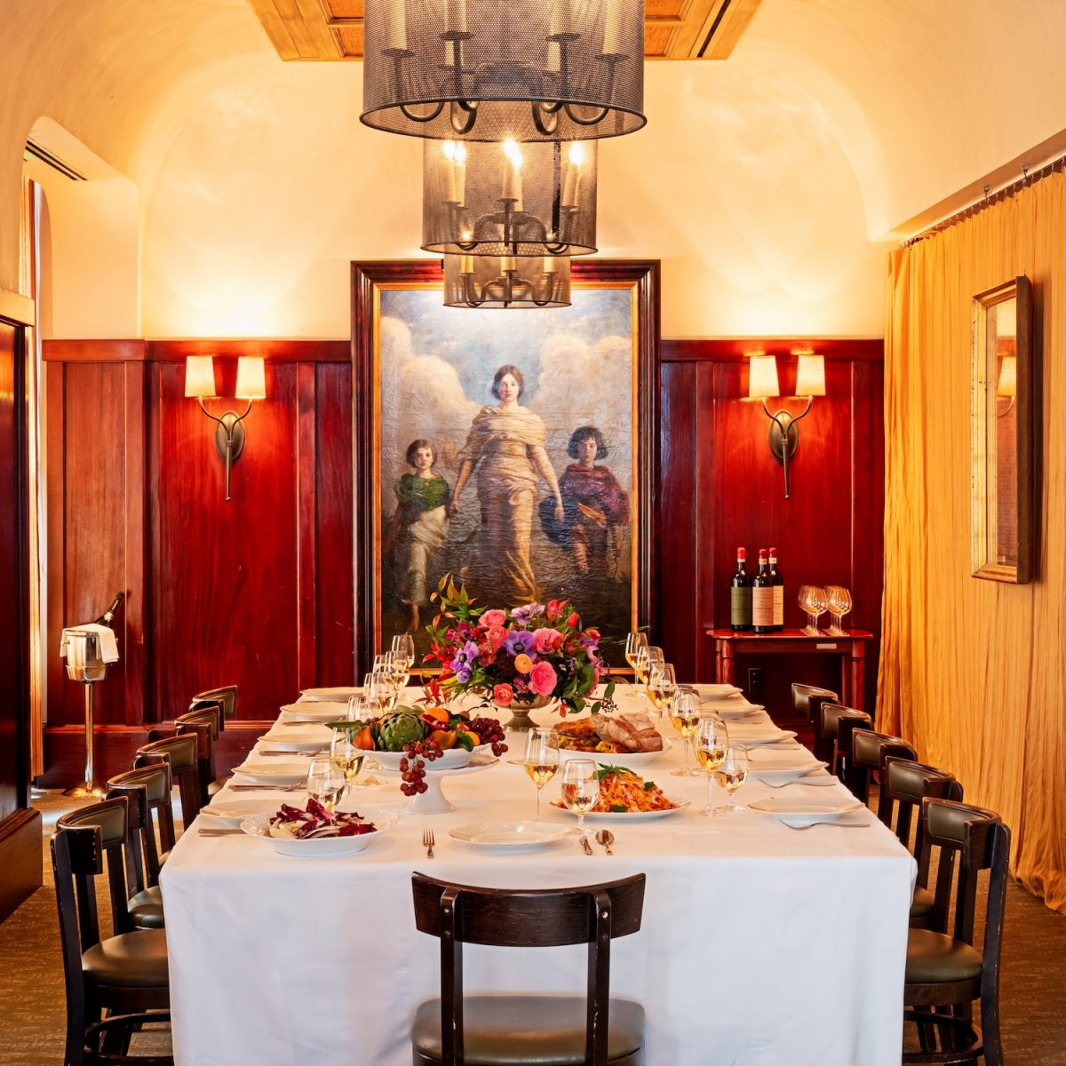 Large table set with white tablecloth, glasses of wine, and platters of food in wood lined private dining room with chandeliers and large painting
