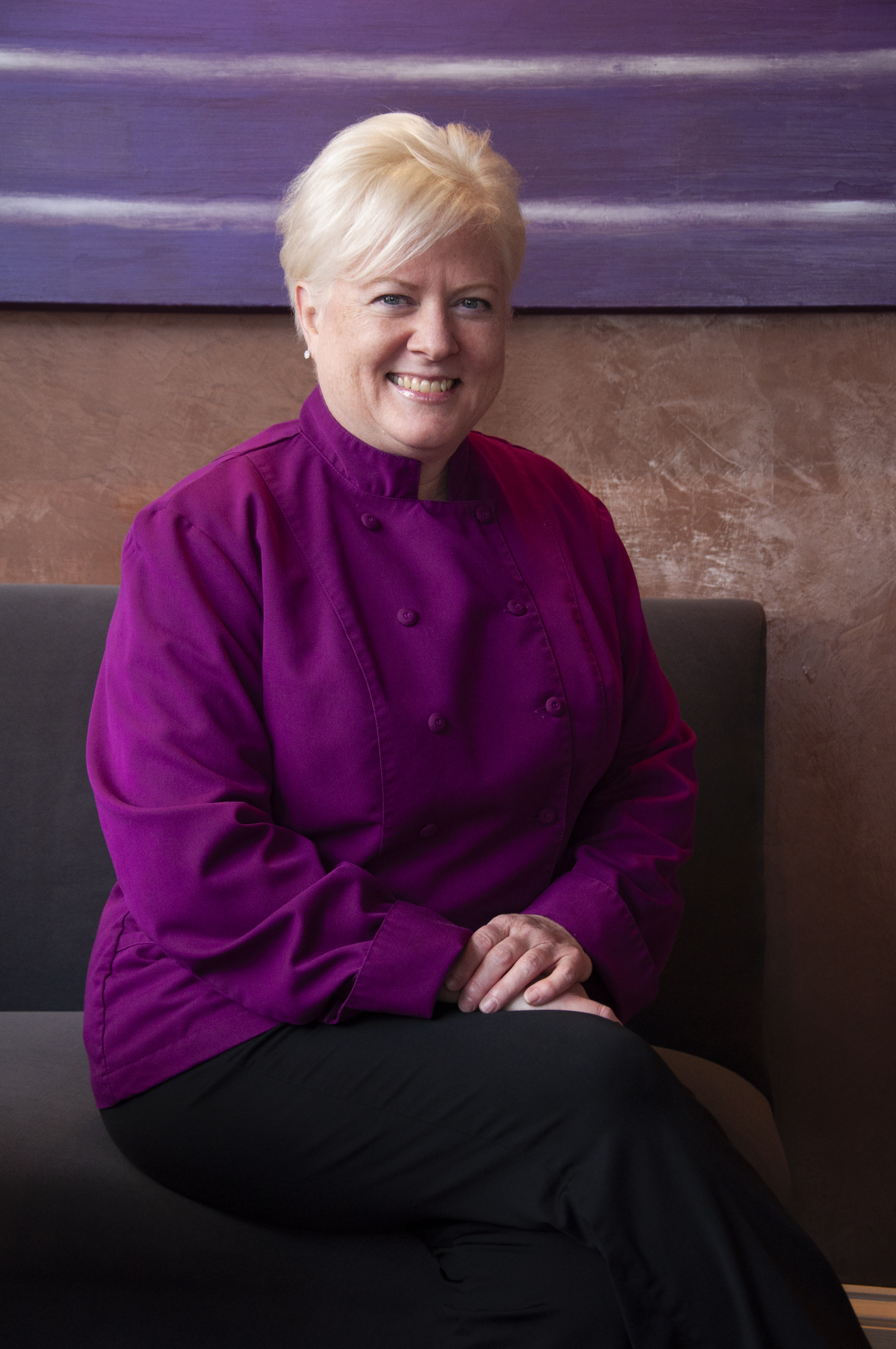 Chef Cindy Wolf in purple chef's jacket seated with legs crossed and hands in lap