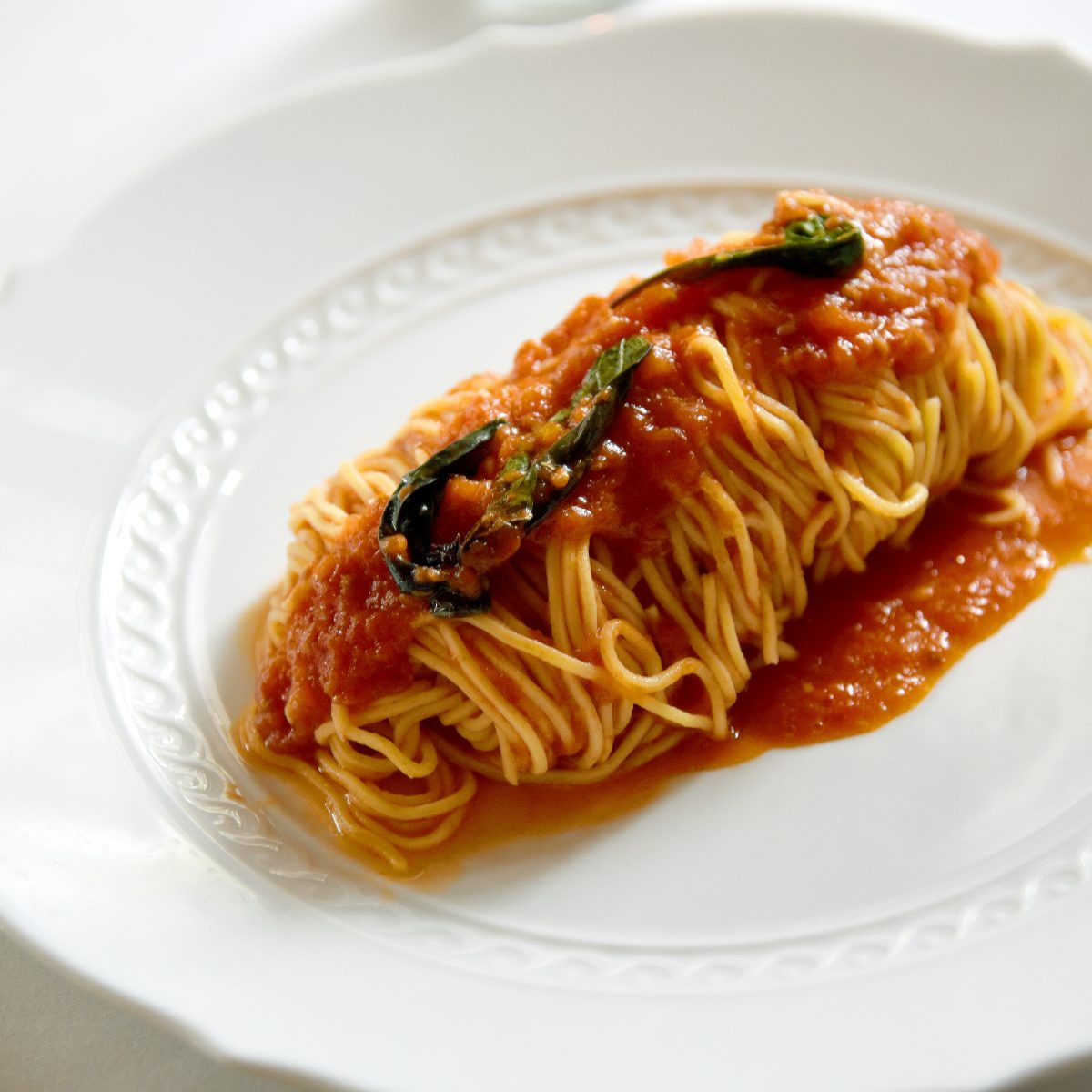 White plate of yellow noodles in red pasta sauce with fresh basil leaves