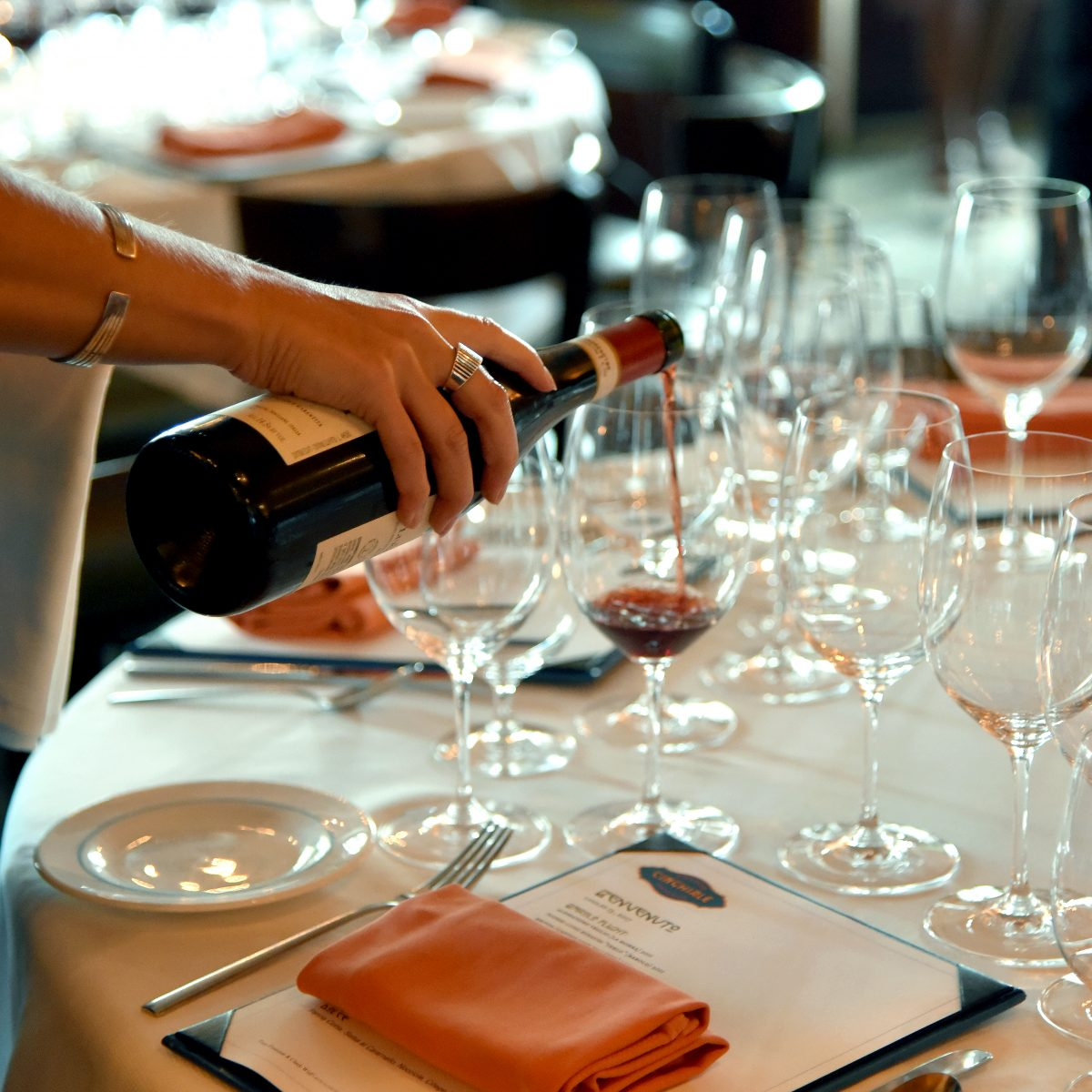 Woman pouring red wine into a glass among many glasses on an elegantly set table
