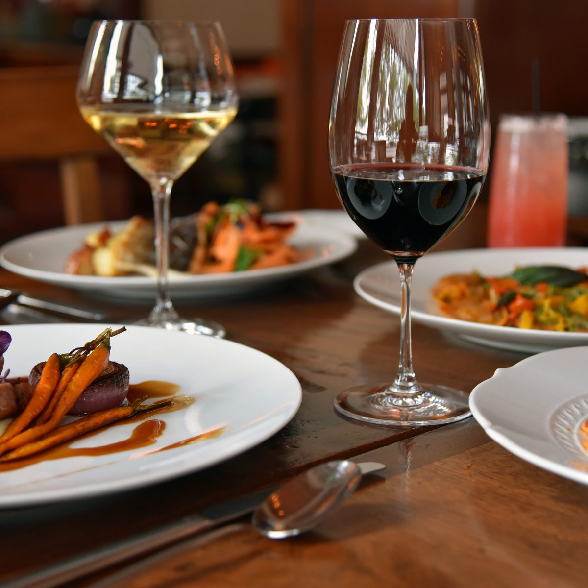 Several plates of pasta, seafood and Italian specialties with wine on a wooden table