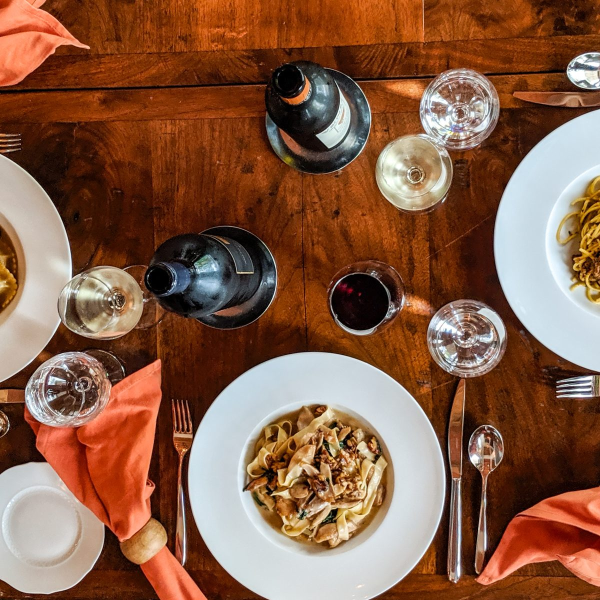 Overhead shot of several dishes of pasta and glasses of wine on a wood table
