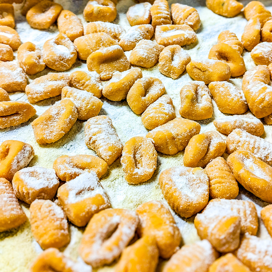 Lots of bright orange sweet potato gnocchi dusted with flour