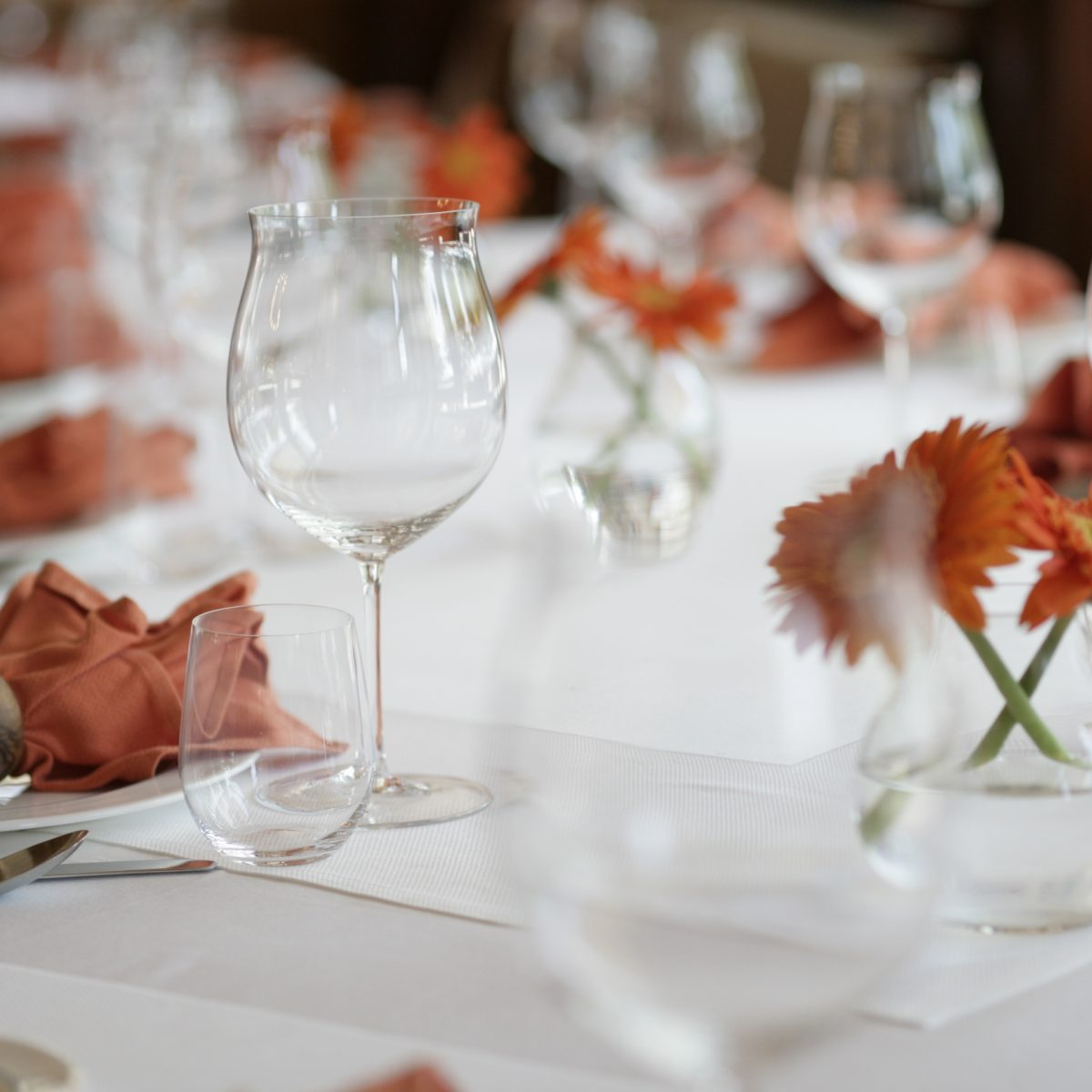 Table set with crystal, china and silver, with orange napkins and orange flowers