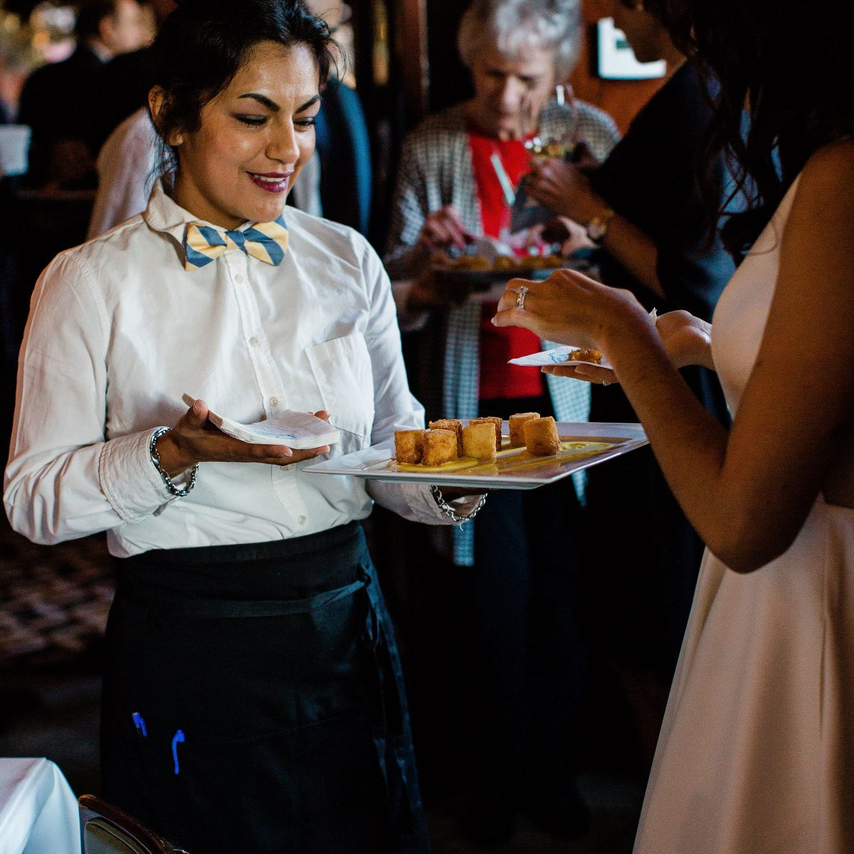 Waitress serving hors d'oeuvres on plate to guest at private event at Cinghiale
