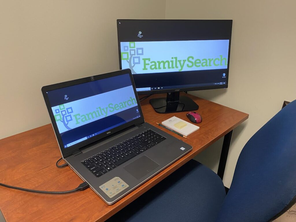 Laptop open with FamilySearch logo on screen and large monitor with FamilySearch logo on screen
